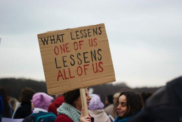 "Demonstrators holding a sign up with the caption ""what lessens one of us lessens all of us"""